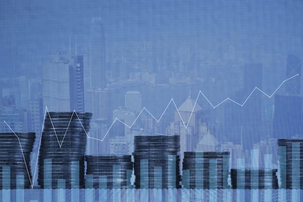 Dubbele belichting stapel van munten met financiële grafiek stad achtergrond