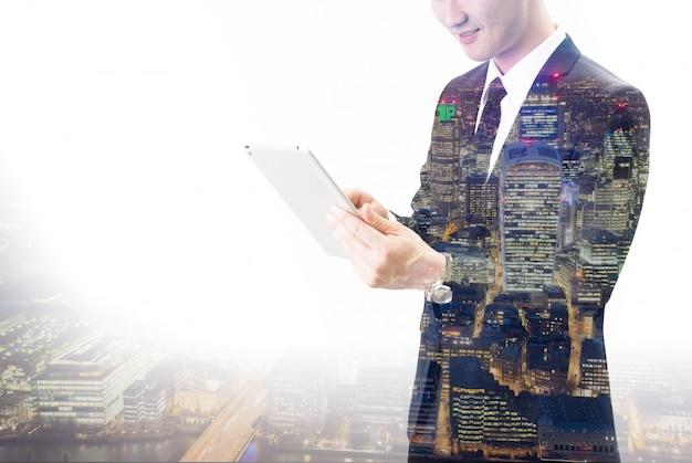 Dubbele blootstelling van aziatische zakenman die de tablet gebruikt