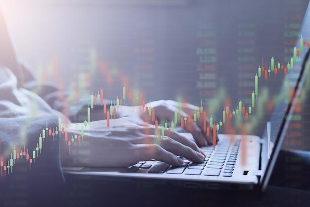 Dubbele blootstelling van close-up handen typen op laptop toetsenbord met financiële grafiek en nummer op de achtergrond van de beurs