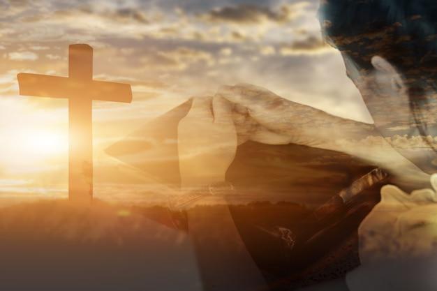 Dubbele blootstelling van een kindmeisje dat de hand aanbidt en god looft bij zonsondergang op de achtergrond. christelijke religie concept.