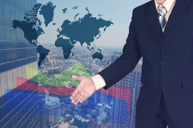 Dubbele blootstelling van zakenman het schudden hand met de grafiek van de de groeigrafiek en de vage bouw en wereldachtergrond