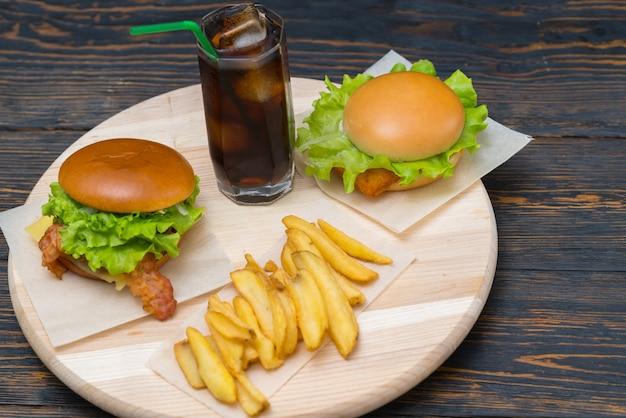 Dubbele kaas- en spekburgers met frisdrank en frietjes geserveerd op een ronde houten plank op een rustieke houten tafel of toog