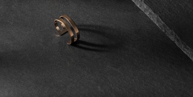 Dubbele vorm moderne gouden ring op donkere stenen ondergrond met kopieerruimte