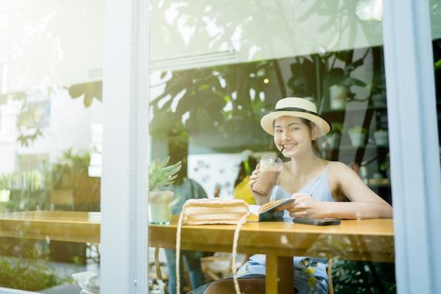 Duidelijke glasbezinning, vrouwenzitting die een boek in een koffiewinkel lezen