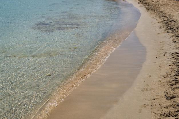 Duidelijke golven en kleurrijk zand op tropisch zandstrand in kreta griekenland.