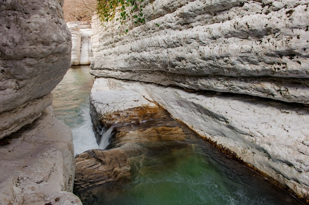 Duidelijke groene bergrivier die onder rotsen in martvili-canion op de herfstdag stromen