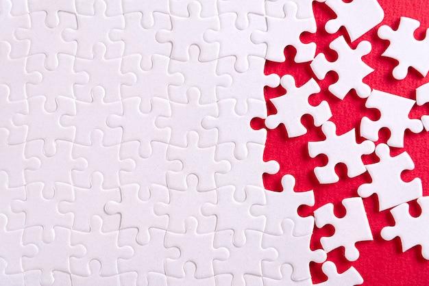 Duidelijke witte puzzel, op rood.
