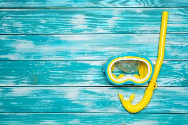 Duikbril en snorkel op houten vloer