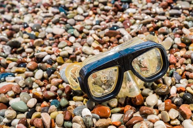 Duikbril op de kiezels