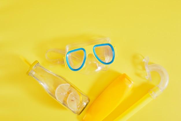 Duikbril, zonnebrandcrème en limonadefles op gele achtergrond, strandvakantie concept bovenaanzicht