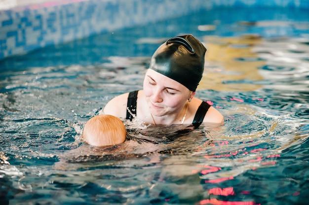 Duikende baby in het peuterbad. jonge moeder, zweminstructeur en gelukkig meisje in pool. leer baby-kind zwemmen. geniet van de eerste dag zwemmen in water. moeder bedrijf baby en duik