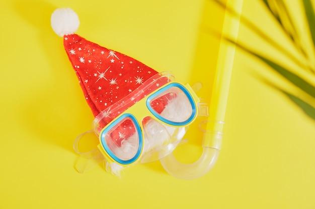 Duikset, kerstman hoed en palmblad op gele achtergrond, kerstvakantie op het strand in een warm land