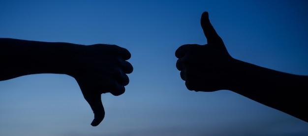 Duim omhoog en duim omlaag hand. twee handen die verschillende gebaren tonen. ja of geen silhouet. leuk en niet leuk teken. keuze. eens of oneens.