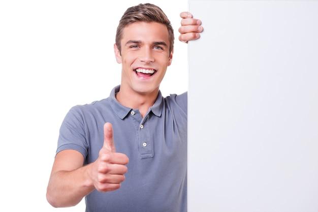 Duim omhoog! gelukkige jonge man die naar de camera kijkt en zijn duim laat zien terwijl hij naar de kopieerruimte leunt en tegen een witte achtergrond staat