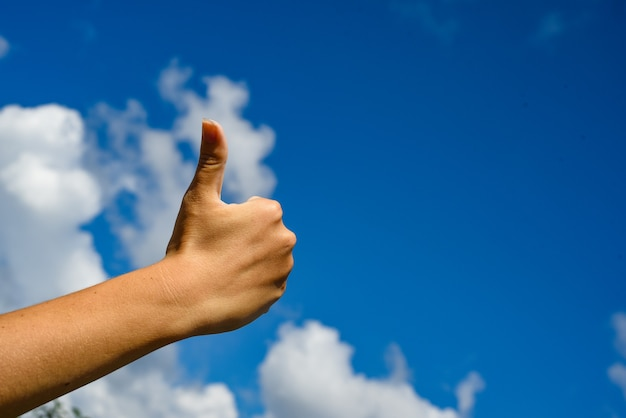 Duim omhoog in de lucht. hand duimen opdagen op een blauwe hemel