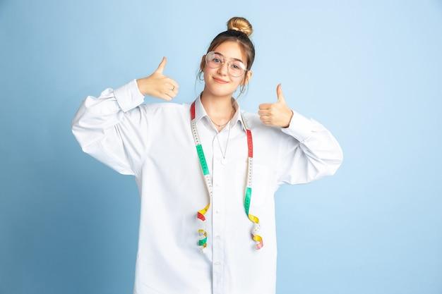 Duim omhoog. jong meisje droomt beroep van naaister. jeugd, planning, onderwijs en droomconcept. wil een succesvolle werknemer zijn in de mode- en stijlindustrie, atelier, maakt kleding.