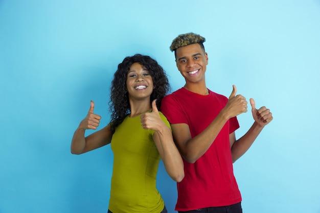 Duim omhoog, lachend. jonge emotionele afro-amerikaanse man en vrouw in kleurrijke kleding op blauwe achtergrond. mooi koppel. concept van menselijke emoties, gezichtsuitdrukking, relaties, advertentie, vriendschap.