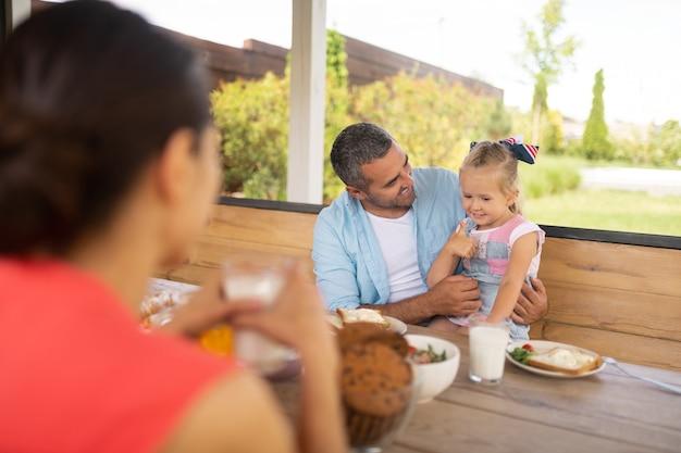 Duim omhoog laten zien. schattige blonde dochter met duim omhoog en opgewonden voor het ontbijt buiten
