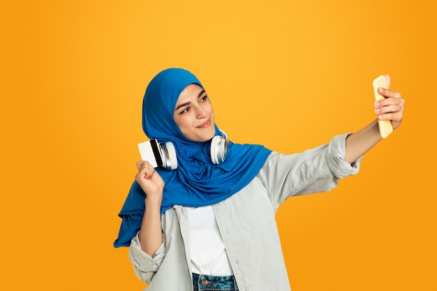 Duim omhoog, luisteren naar muziek. jonge moslimvrouw op geel. stijlvol, trendy en mooi vrouwelijk model