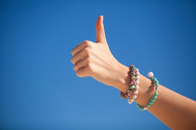 Duim omhoog teken op de hand van een vrouw tegen de turquoise zee