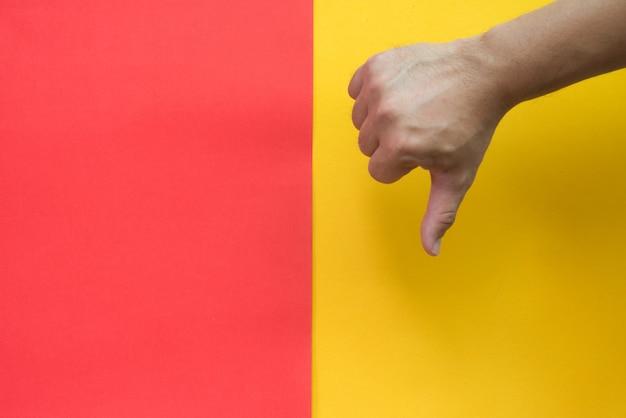 Duim omlaag op rode en gele achtergrond.