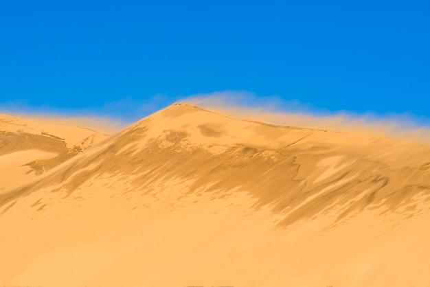 Duin tegen de achtergrond van een helderblauwe lucht de wind blaast het zand van de nok van de duinâ wilde natuur landschap bureaubladachtergrond