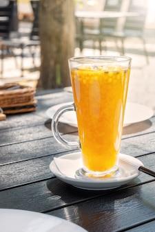 Duindoorn en sinaasappelthee in een openluchtrestaurant. geel drankje op de tafel van een straatcafé.