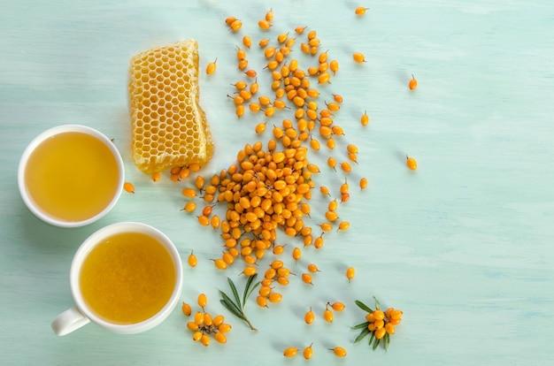 Duindoorn, honing en kopje thee met duindoorn