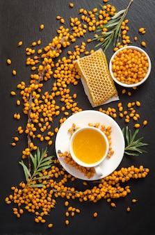 Duindoorn, honingraat met honing en een kopje thee op de zwarte stenen tafel