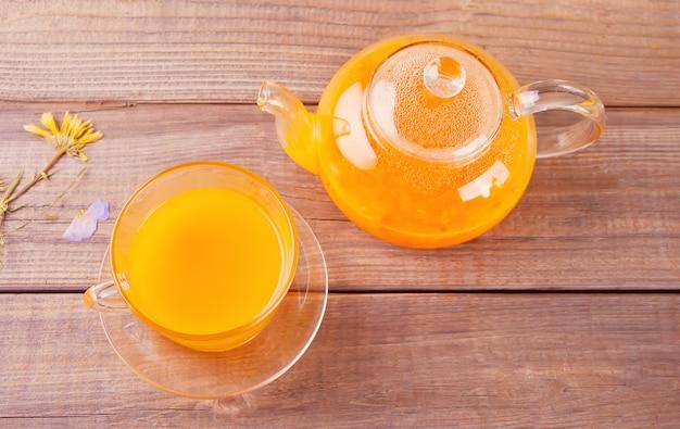 Duindoorn thee in een glazen beker.