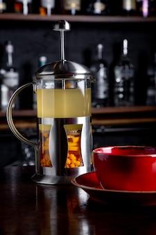 Duindoorn thee in franse pers met honing op een houten tafel bij coffeeshop.