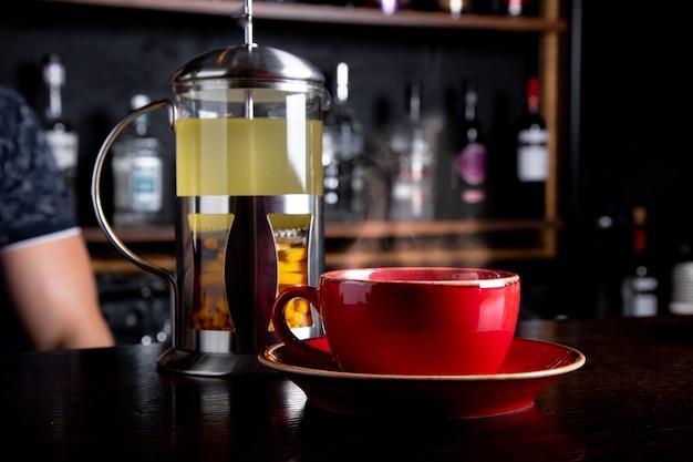 Duindoorn thee in franse pers met honing op een houten tafel bij coffeeshop