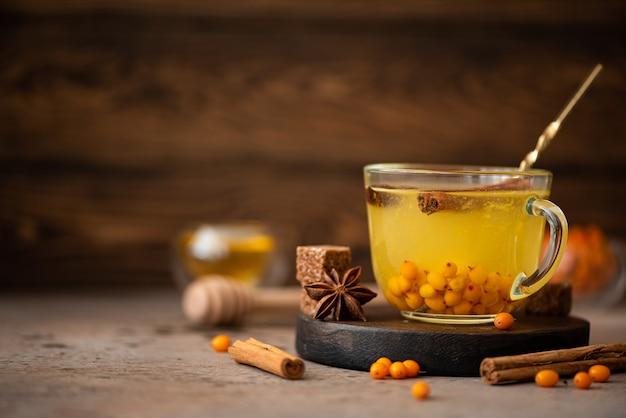 Duindoorn thee met honing en kruiden in een glazen mok op een houten tafel