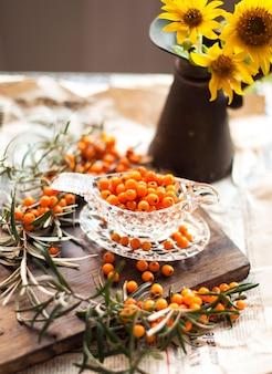 Duindoornbessen zijn vers en een tak met bladeren. oude foto. vitaminen en gezondheid. boeket zonnebloemen