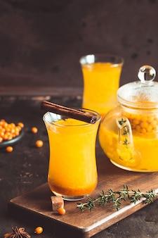 Duindoorndrank in de herfst of winter. duindoorn thee. stilleven, eten en drinken, seizoensgebonden en vakantie concept. de herfst hete drank in een glas