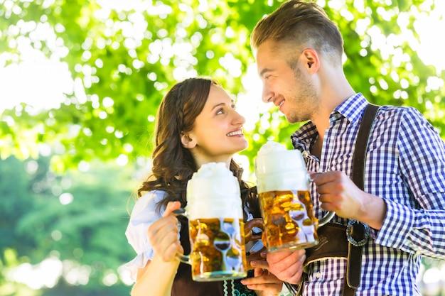 Duits paar in tracht bier drinken