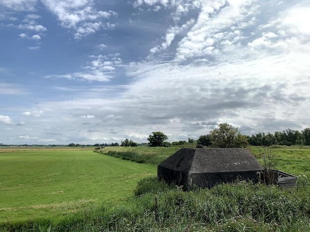 Duitse bunker, kazemat in nederlands landschap als onderdeel van een verdedigingsmuur