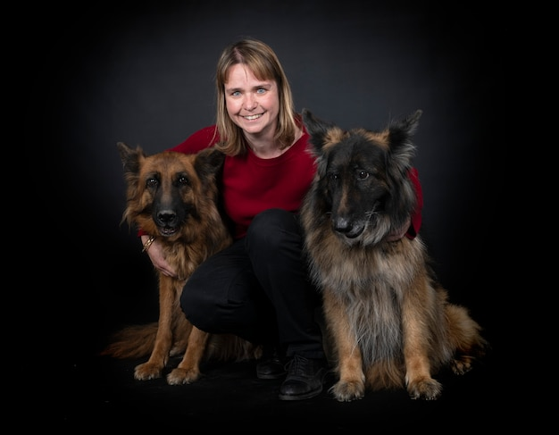 Duitse herders en vrouw voor zwarte achtergrond