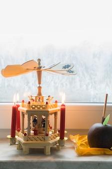 Duitse kerst houten piramide met geglazuurde appel op vensterbank