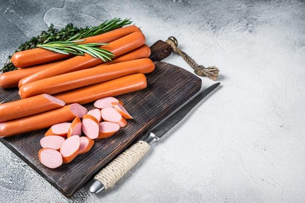 Duitse rauwe frankfurter worstjes op een houten bord