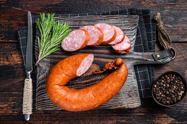 Duitse rookworst op een rustieke houten bord met tijm. donkere houten achtergrond. bovenaanzicht.