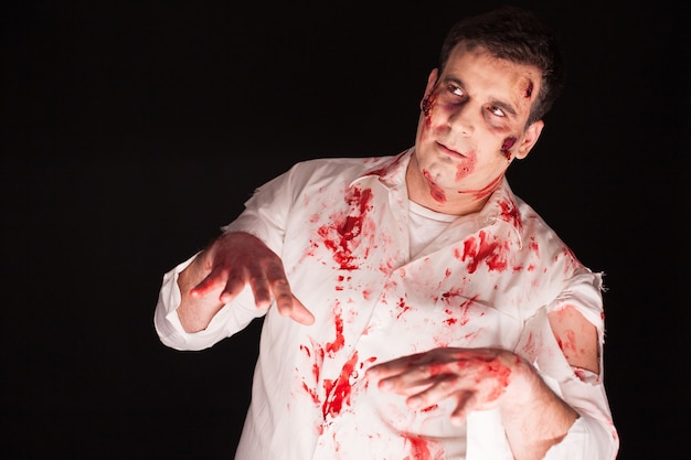 Duivel in een man met bloedige creatieve make-up op zwarte achtergrond. halloween kostuum.