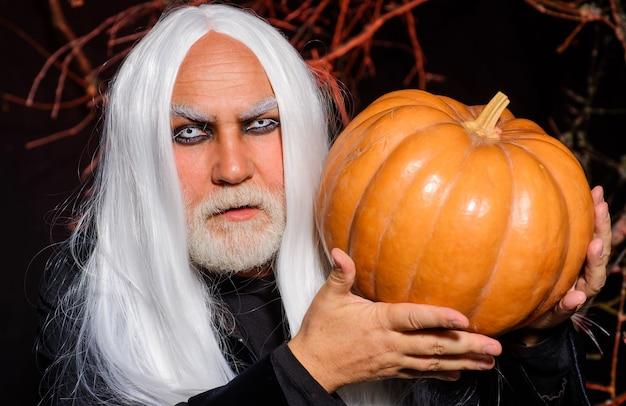Duivel man met jack-o-lantern. fijne halloween. kwade tovenaar met oranje pompoen. bebaarde man klaar voor halloween-feest.