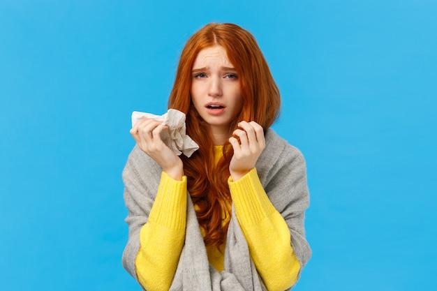Duizelig, ongemakkelijk triest roodharige vrouw draagt sjaal om warm te worden, verkouden, niest en een loopneus heeft, servet gebruikt, camera kijkt met uitgeputte vermoeidheid, vermoeidheid voelt, blauwe achtergrond