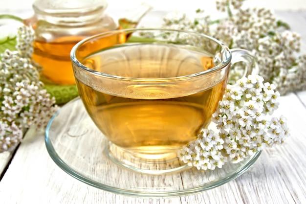 Duizendblad thee in een glazen beker en theepot, verse duizendblad bloemen op een licht bord