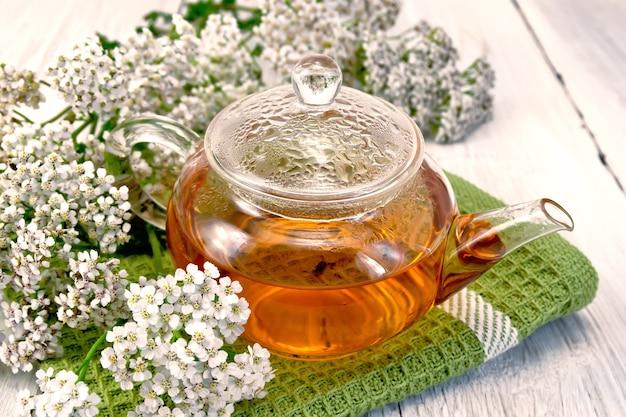 Duizendbladthee in een glazen theepot op een groen servet, verse duizendbladbloemen op een bleke houten plank