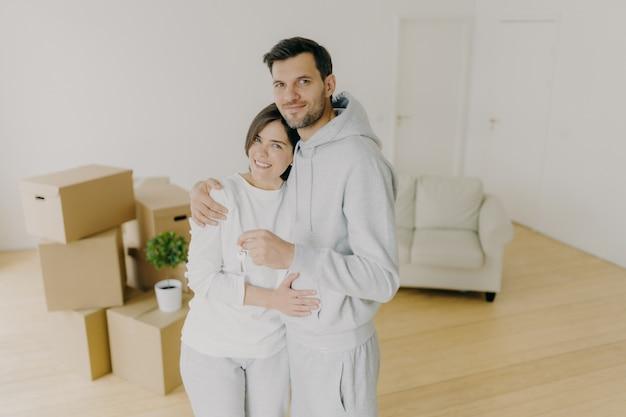 Duizendjarig echtpaar met aangename glimlach, knuffel en houd sleutel van eigen appartement