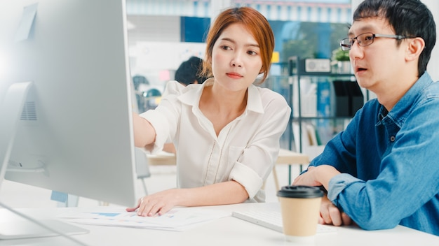 Duizendjarige groep jonge aziatische zakenman en onderneemster in klein modern stedelijk bureau. japanse mannelijke baas supervisor die stagiair of nieuwe werknemer koreaans meisje onderwijst dat helpt met moeilijke opdracht.
