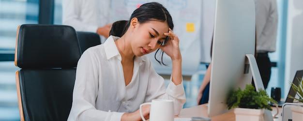 Duizendjarige jonge chinese zakenvrouw werken stress uit met project onderzoeksprobleem op computer desktop in vergaderzaal op kleine moderne kantoor. azië mensen beroepsgebrek syndroom concept.