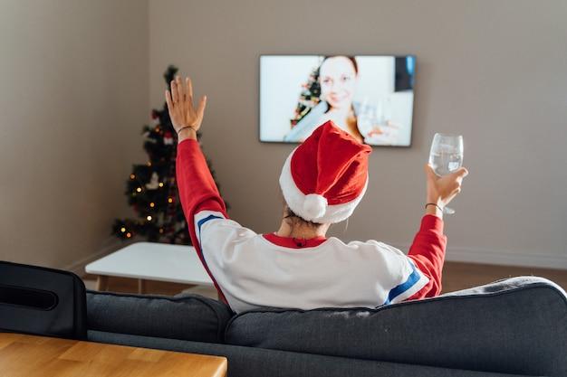 Duizendjarige jonge vrouw met behulp van telefoon thuis op kerstavond. online kerstinkopen, quarantaine